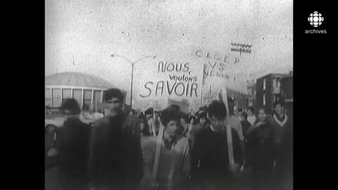 Jeunes marchant avec des pancartes dont deux portent les messages «Nous voulons savoir» et «Cégep vs Avenir».