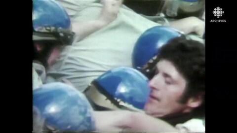 Policiers à casques bleus à travers les manifestants.