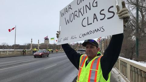 Un homme tient une pancarte sur le trottoir.