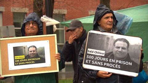 Deux personnes tenant des affichettes appelant à la libération d'un journaliste emprisonné
