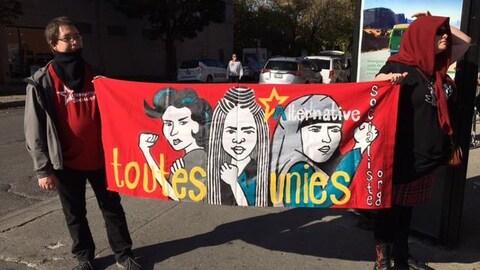 Des manifestants tiennent une banderole affichant le slogan « Toutes unies ».