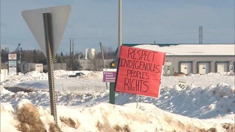 Une affiche demandant le respect des droits autochtones est plantée dans la neige.