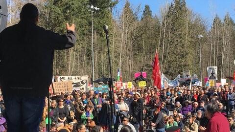 Un homme parle sur scène à des manifestants
