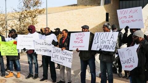 Des personnes manifestent devant le Musée canadien pour les droits de la personne.