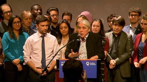 Manon Massé parle dans un micro, entourée de plusieurs délégués et de Gabriel Nadeau-Dubois.