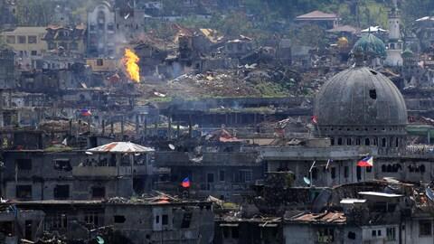 Des flammes s'élèvent dans des édifices de Marawa City, aux Philippines, le 23 octobre 2017, après que des troupes gouvernementales philippines ont libéré la ville de combattants membres du groupe armé État islamique.