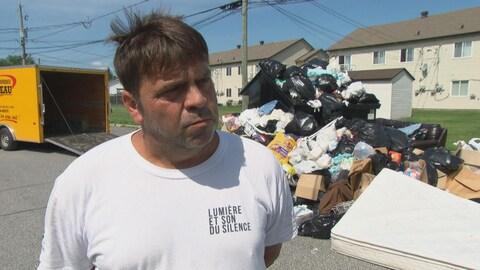 Marc Carrière répond aux questions d'un journaliste devant un amas de déchets encombrants.