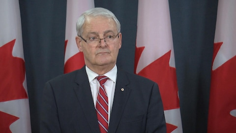 Marc Garneau lors d'une conférence de presse devant des drapeaux canadiens.