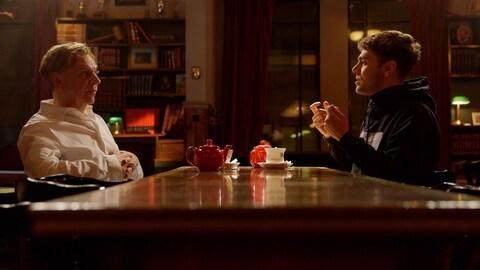Les deux hommes sont assis face à face devant des tasses de thé.