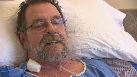 Une homme portant des lunettes en entrevue dans sa chambre d'hôpital.