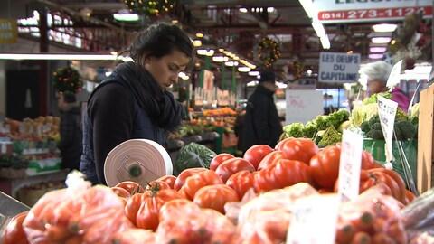 Une jeune femme replace un étale de légumes au marché Jean-Talon, à Montréal.
