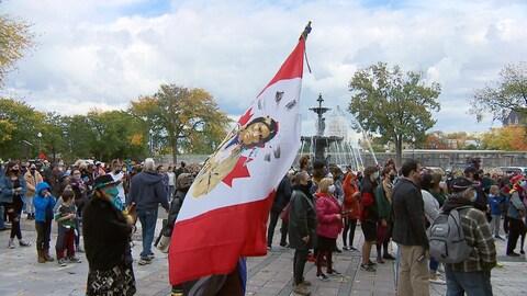 Gros plan sur un drapeau autochtone dans une manifestation. On voit plusieurs personnes derrière.