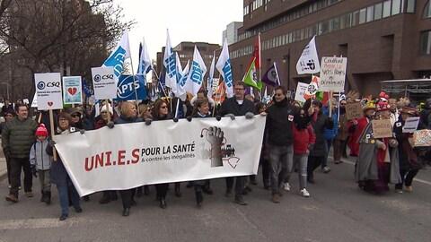 Des manifestants tiennent une affiche où on peut lire «uni.e.s pour la santé et contre les inégalités»