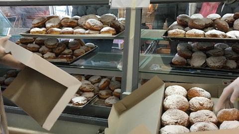 Des boîtes sont remplies de paczkis dans le comptoir d'une boulangerie.