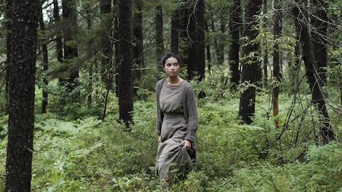 Une jeune femme marche seule en forêt.