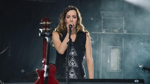 L'auteure-compositrice-interprète Marie-Clô chante debout sur une scène derrière son clavier