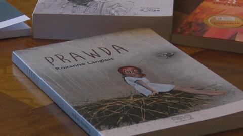 Le livre Prawda de l'auteure Roxanne Langlois est posé sur une table.