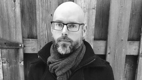Portrait en noir et blanc du poète Mario Brassard, à l'extérieur, devant une palissade de bois. Il a le crâne rasé et porte une barbe et des lunettes, ainsi qu'un manteau et un foulard autour du cou.