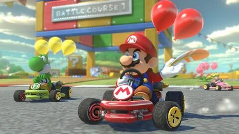 Une capture d'écran du jeu Mario Kart 8 montrant les personnages de Mario, Yoshi et Peach en pleine course de karts.