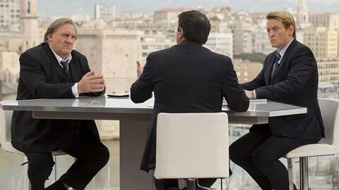 Trois hommes sont autour d'une table en train de débattre.