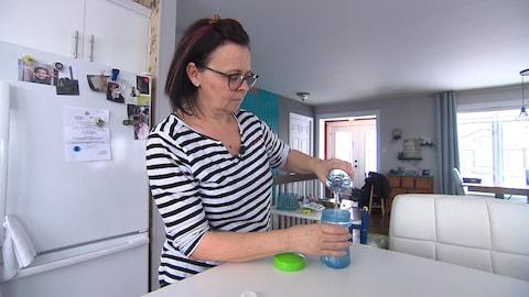 Martine remplit un biberon d'eau de source.