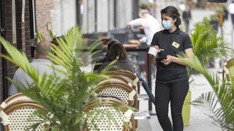 Quelques clients assis à une terrasse d'un restaurant et une serveuse portant un masque.