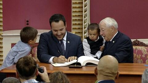 Mathieu Lacombe qui signe un livre, entouré de sa famille.