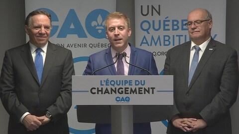 Les trois sont devant des panneaux affichant les couleurs de la CAQ.