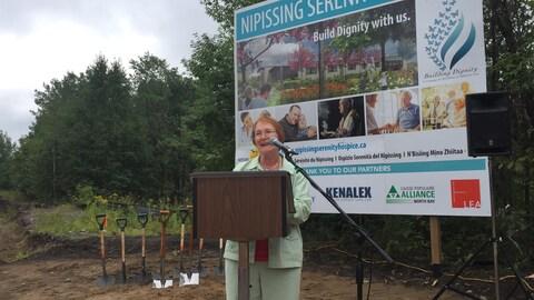 Mathilde Gravelle Bazinet prononce un discours derrière un podium devant la pancarte annonçant la construction de la maison Nipissing Serenity Hospice.