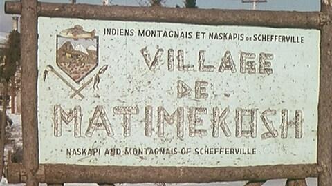 Un panneau en rondins sur lequel on peut lire Village de Matimekush, indiens montagnais et naskapis de Schefferville