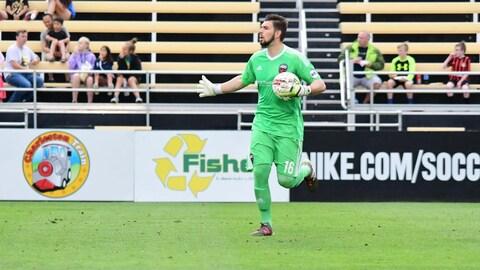 Un gardien de soccer court avec le ballon dans une main.