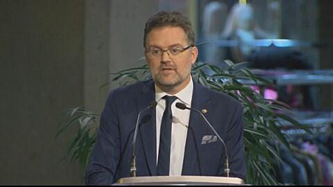 Maxime Pedneaud-Jobin fait un discours devant un pupitre lors de la cérémonie d'assermentation des élus municipaux de Gatineau à la Maison du citoyen.
