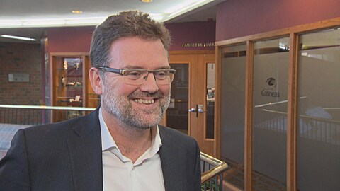 Le maire sourit devant son bureau à la Maison du citoyen.