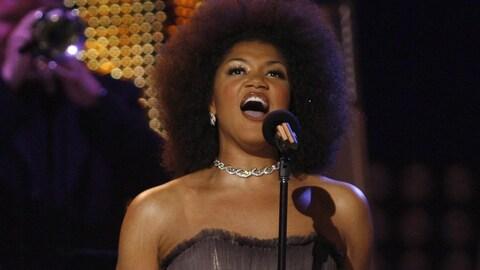 La femme chante sur scène.