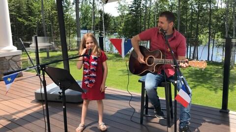 Une jeune fille et son père, guitare en main, chantent.