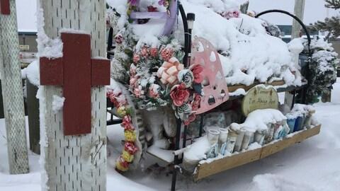 Des fleurs et des bougies ont été disposées devant l'école secondaire de La Loche.