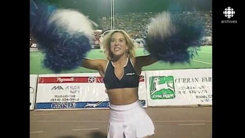 Jeune femme munie de pompons qui danse dans un stade.