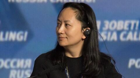 Une femme asiatique porte une oreillette et regarde vers sa droite. Elle est vêtue en noir.