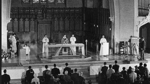 Prêtre qui célèbre une messe et fidèles qui écoutent.