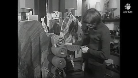 Un homme se tient debout à côté de rouleaux de tissus et observe la fibre.