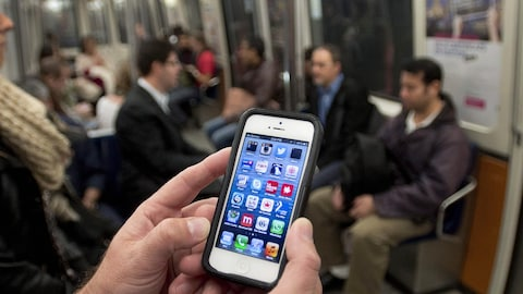 Un homme regarde son téléphone mobile dans un wagon de métro.