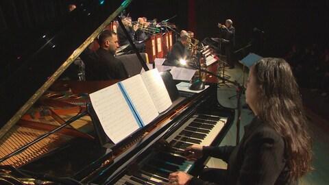 Michelle Grégoire jouant du piano et accompagnée de l'orchestre de jazz de Winnipeg.