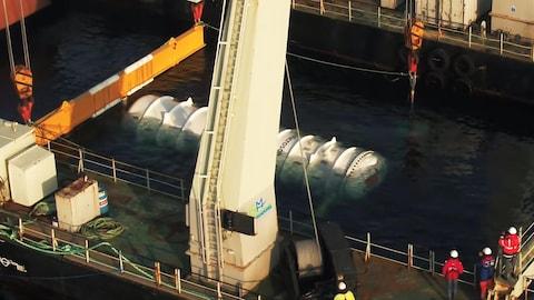 Une capture d'écran d'une vidéo montrant la capsule de Microsoft, attachée à une grue flottante, en train de descendre vers les profondeurs marines.