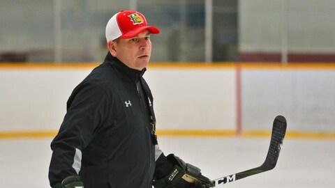 Jim Midgley bâton de hockey en main patine dans un aréna