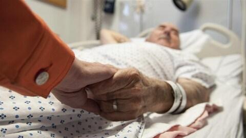 Un patient alité tient la main d'une personne.