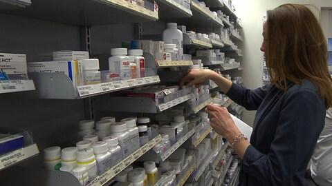 Une pharmacienne vérifie l'étiquette de flacons de médicaments sur une étagère.