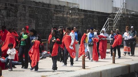 Des dizaines de migrants marchent le long d'un quai dans le port de Tarifa avec des couvertures fournies par la Croix rouge espagnole.