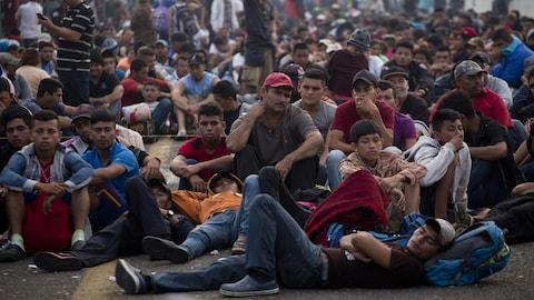 Des migrants honduriens assis sur le pont qui sépare le Mexique du Guatemala