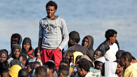 Plusieurs hommes attendent de descendre d'un bateau. L'un d'eux surplombe les autres.