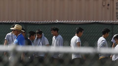 De jeunes hommes marchent à l'intérieur d'un périmètre clôturé.